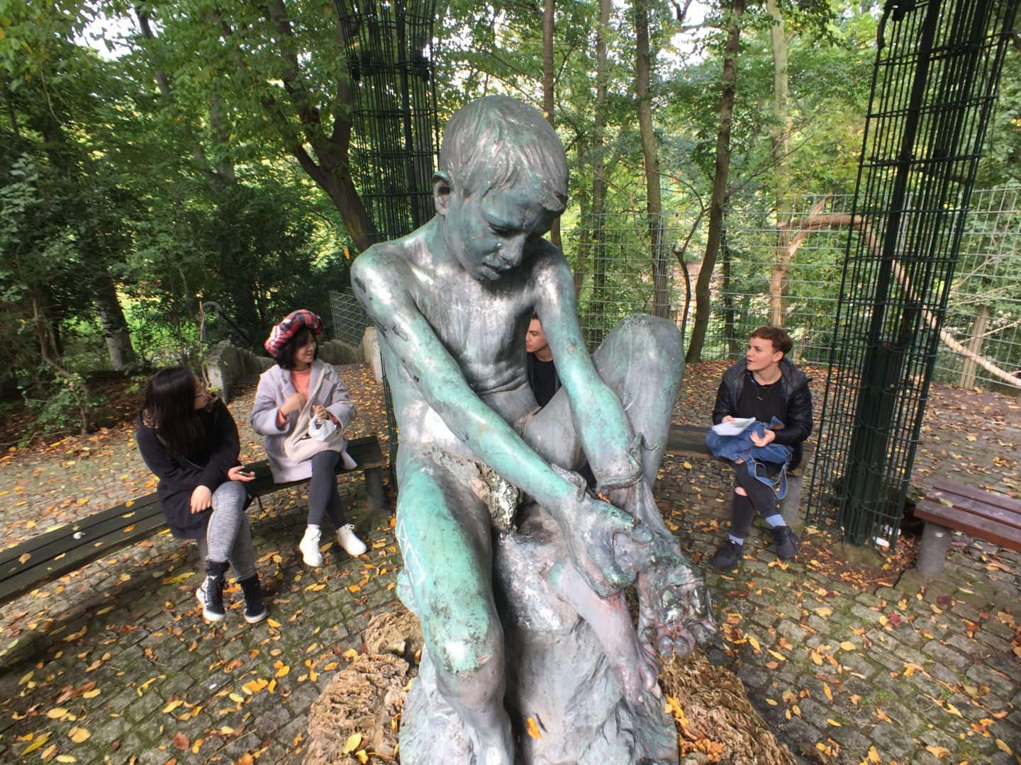 In the foreground is the sculpture of a boy fighting to remove an octopus from his left hand. The boy's face shows more resolve than fear. The sculpture is green bronze. In the background is a group of four people, sat on the bench chatting and having some lunch. The ground is covered in leaves. It is October and getting chilly.
