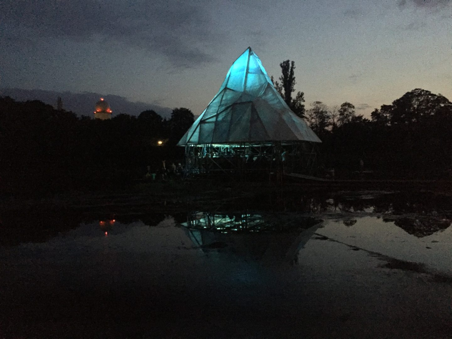 The Floating University pictured at night. The depicted structure is illuminated light blue and resembles an iceberg. It is surrounded by darkness. Water in the foreground reflects the light.